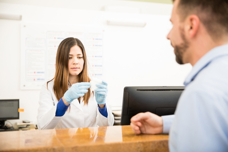 Good looking receptionist labeling a urine sample from a male patient in a laboratory front desk