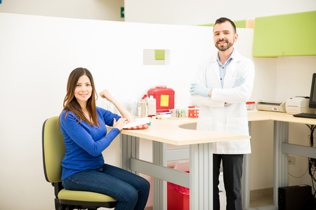 Portrait of a good looking doctor and female patient smiling after getting a blood test in a clinic