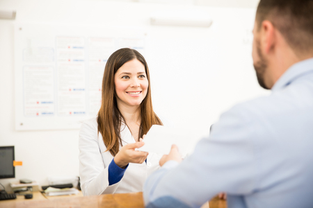 Pretty receptionist handing over lab test results to a patient with a smile