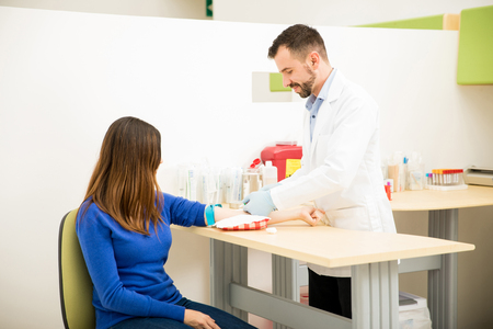 Male Hispanic doctor about to draw some blood from a female patient in a laboratory