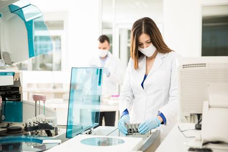 Kijkende chemici kijken druk terwijl ze bloedonderzoeken uitvoeren in een klinisch laboratorium