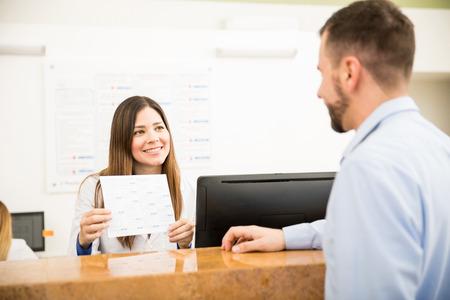 Portret van een mooie receptioniste die de beschikbare diensten en kosten voor een klant toont, met een glimlach Stockfoto