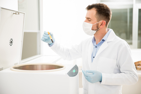 Profile view of a good looking male chemist using a centrifuge to analyze some blood in a lab