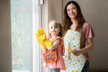 mandil: la familia feliz joven hispana orgullosos de sus tareas domésticas cerca de la ventana Foto de archivo
