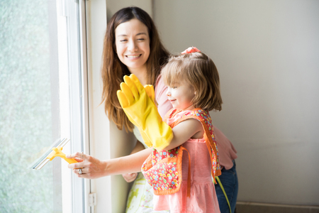 bravo: Cute adorable girl claps using gloves while her pretty mother cleans the window from inside the house Stock Photo