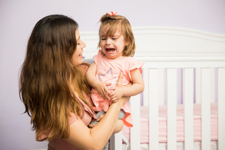 Gorgeous Hispanic woman trying to make her angry child stop crying in the nursery