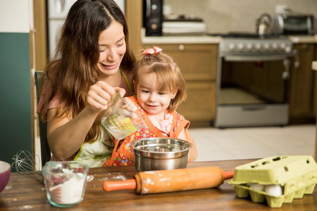 Sweet little child excited adding ingredients with her cute mother in the kitchen Banco de Imagens