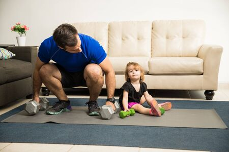 Sweet little girl training with her handsome Hispanic father at home