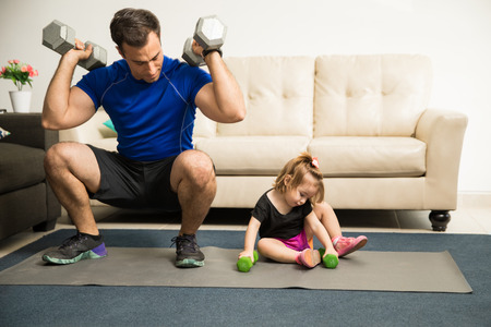 Attractive fitness father showing his strength while his sweet daughter tries to imitate him in the living room