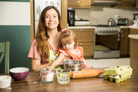 Proud good looking Latin mom trying to do some cooking while her little girl distracts her in the kitchen Banco de Imagens