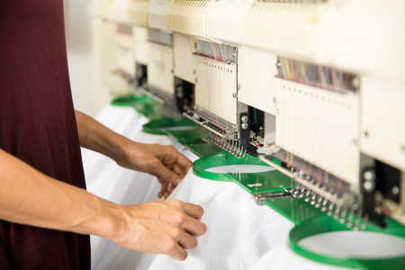Closeup of a woman placing several garments on an embroidery machine in a textile factory Stock Photo