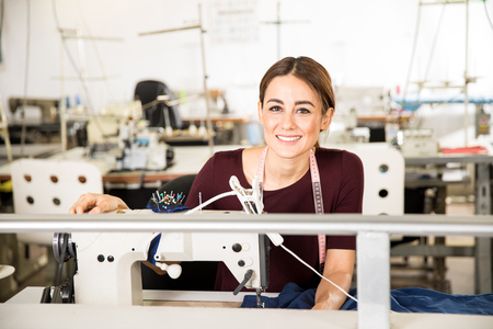 Portrait of a gorgeous young seamstress sitting in front of a sewing machine in a textile factory and smiling