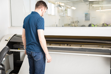 Rear view of a young man waiting for a plotter to print his work in a workshop