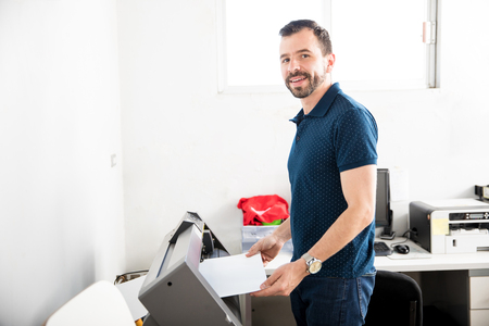 Attractive young Latin worker using a plotter to print some labels for a serigraph press Stock Photo