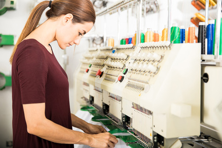Profile view of a woman putting many garments in place in an embroidery machine at a factory Stockfoto