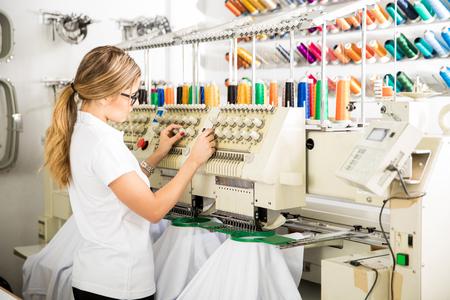 Jonge vrouwelijke werker bereiden draad en kleding in een borduurmachine in een fabriek Stockfoto