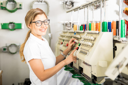 Profile view of a cute female worker setting up some thread rolls in an embroidery machine at a factory