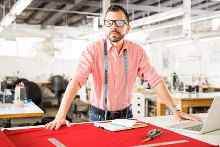 Portrait of a confident and powerful fashion designer doing some work in his workshop