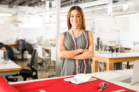 Pretty and successful Hispanic fashion designer standing in her workshop and smiling Stock Photo