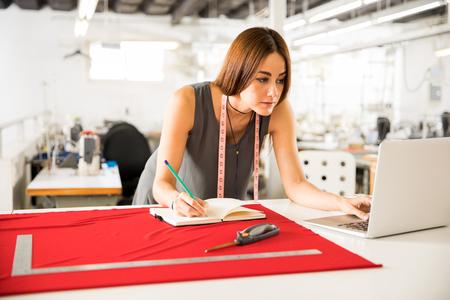 Aantrekkelijke jonge modeontwerper met behulp van een laptopcomputer en werken aan een schets Stockfoto