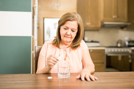 Senior adult Latin woman calming her stomachache with an effervescent antiacid tablet on water Stock Photo