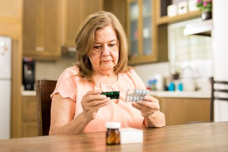senior adult woman: Good looking senior adult woman looking at her pills expiration date sitting in the kitchen Stock Photo