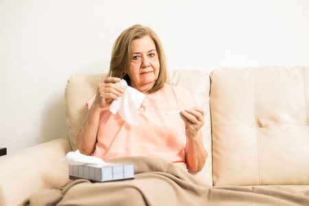 Elder grandmother sick with cold checking her temperature sitting in the living rooms sofa