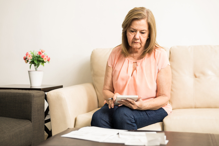 Beautiful Hispanic elder lady checking her personal finances from bills and savings at home