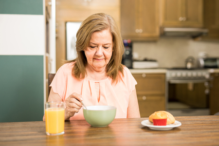 Pretty senior woman sitting in the kitchen and without appetite for breakfast Stock Photo