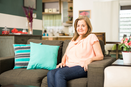 senior adult woman: Pretty joyful senior adult woman sitting alone on the living rooms couch in the morning