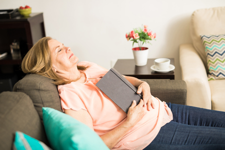 Good looking nostalgic Latin retired grandmother resting on her couch with a book in her hands