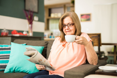 senior adult woman: Good looking senior adult woman holding a coffee cup while she updates with news in the living room