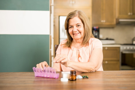 Pretty Hispanic senior woman adding pills to her pill box to complete the week of medicines following the doctors prescription