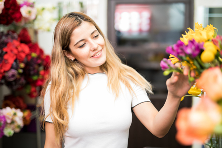 Attractive cute woman delighted by the colors of a bunch of flowers on display in a florist shop