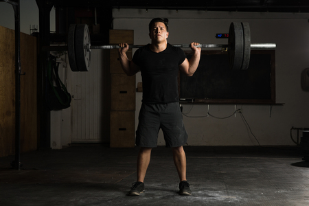 Full length view of a young Latin sportsman doing barbell squats in a cross-training gym