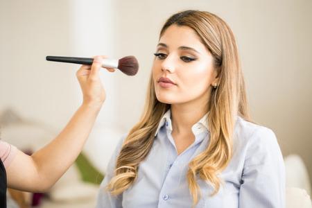Apuesto joven mujer de raza caucásica de pie delante de un espejo al hacer su maquillaje en un salón de belleza