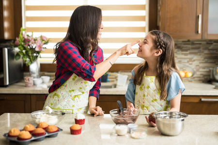 Profile view of a cute girl having fun with her mom in the kitchen while baking and decorating cupcakes with frosting