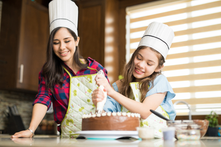 Pretty girl with a chefs hat decorating a cake she just baked with her mom at home