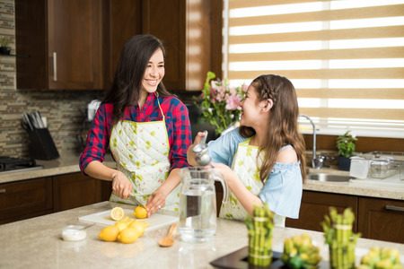 Portrait of a cute young single mom and her daughter making lemonade and having a good time together in the kitchen Zdjęcie Seryjne