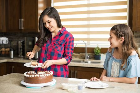 Attractive mother slicing and serving cake for her daughter in the kitchen