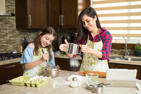 ヒスパニック系のかわいい母娘に役立ちます彼女のいくつかのケーキのねり粉を混合しながら台所でいくつかの小麦粉をふるい分けの肖像