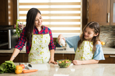 Pretty girl and her mother eating a freshly made salad together in the kitchen Banco de Imagens