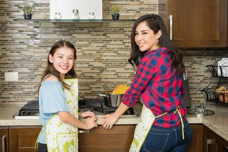 matching: Cute Hispanic young woman and her daughter wearing matching aprons and cooking pasta at home