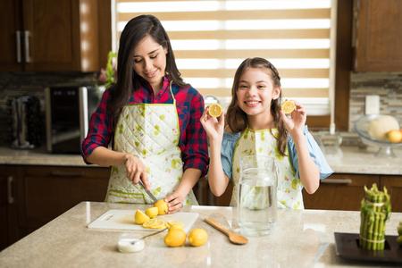 Leuk meisje die haar moeder in de keuken helpen en wat pret hebben die limonade maken Stockfoto