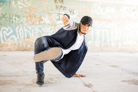 Good looking young hip hop dancer practicing a dance routine in an urban setting with graffiti walls Stok Fotoğraf
