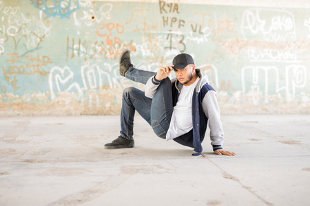 Handsome Latin breakdancer showing some of his dance moves in front of a graffiti wall