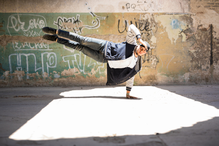 Handsome male hip hop dancer doing a handstand and making eye contact in an urban setting Фото со стока