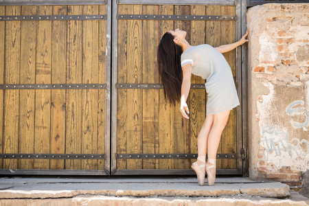 barndoor: Profile view of a beautiful young ballerina standing en point and enjoying ballet in an urban setting
