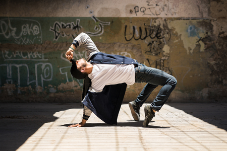 Young male hip hop dancer arching back and showing some of his dance moves in an urban setting with graffiti walls