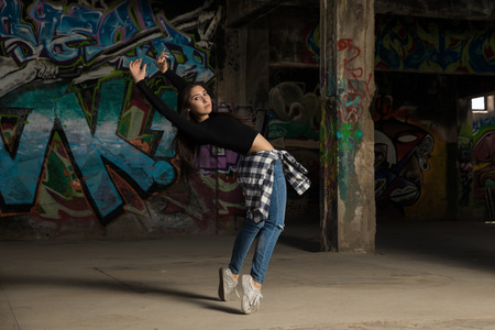 Beautiful urban dancer standing on her toes while dancing in front of a graffiti wall Banque d'images